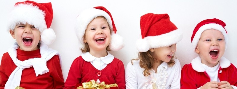 Four kids with Christmas hats, having fun, and laughing.