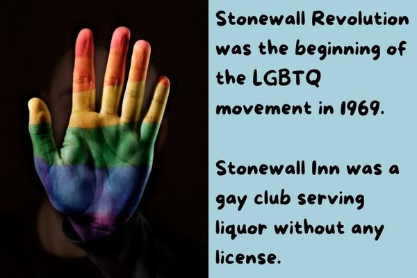 An hand with the LGBT flag on painted on it.