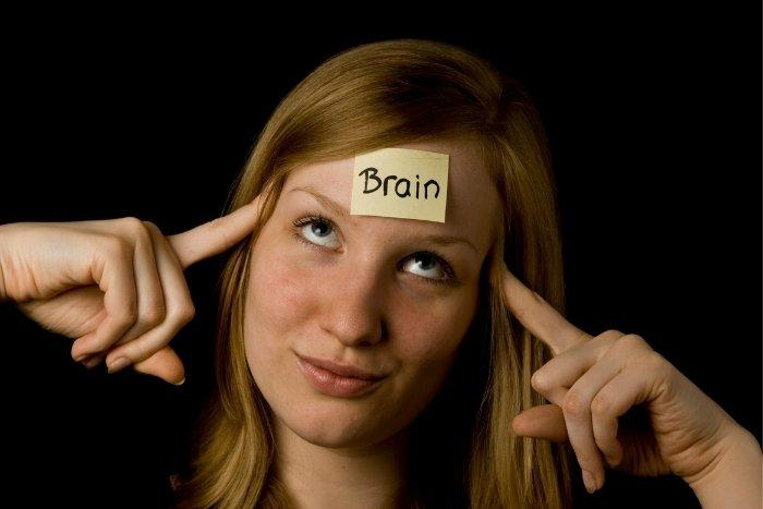 A woman with a note with the word brain on her forehead.
