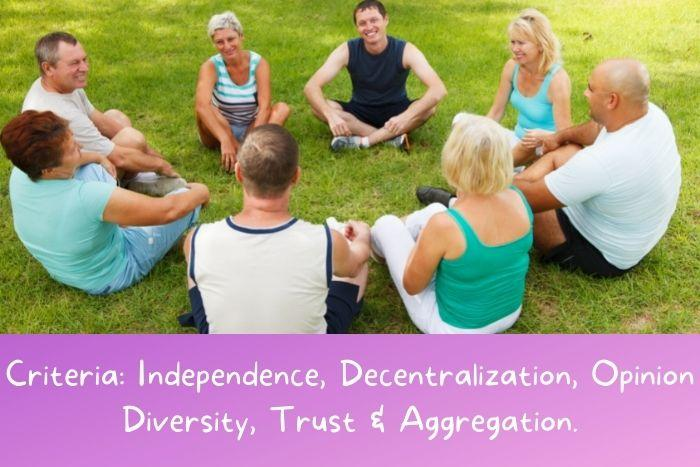 A diversified group of people is sitting on the grass and talking.