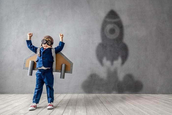 A young boy with a rocket flying up with his motivation.