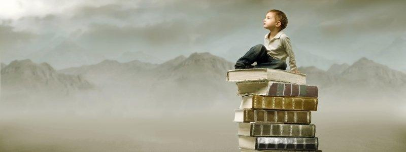 A kid on a mountain of books think about the answer to the questions how to educate yourself