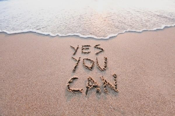 "Motivation quote - ""yes you can"" written on the beach sand near the sea."