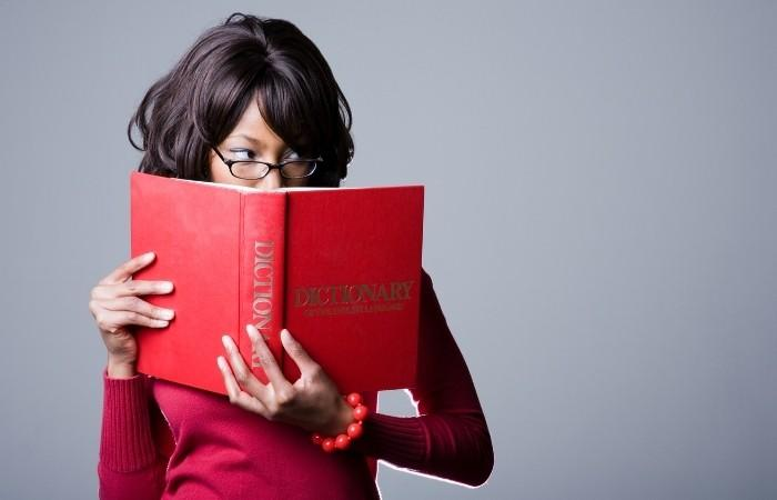 A funny woman looking behind a dictionary while it covers her face.