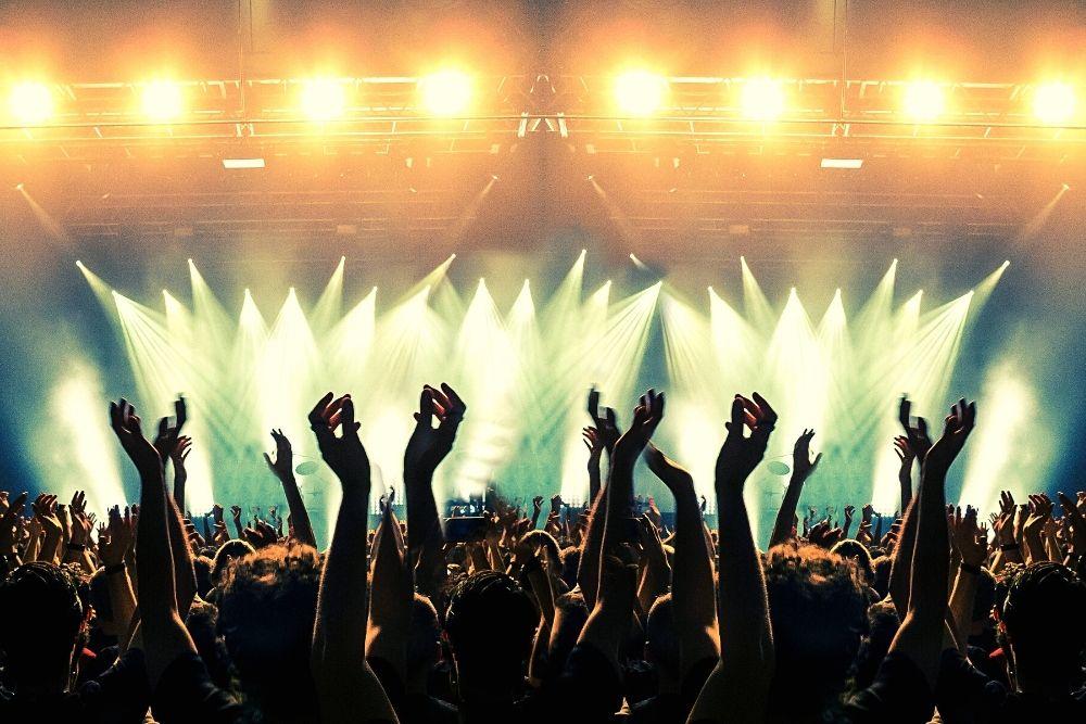 Fans raising their hands in a music concert.