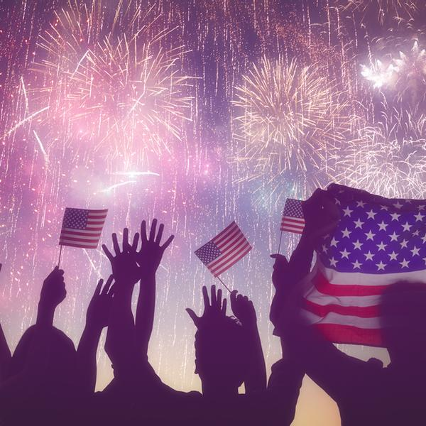 People with American flags watching fireworks on the 4th of July.