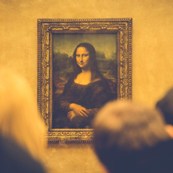 People at an art museum looking at the Mona Lisa.