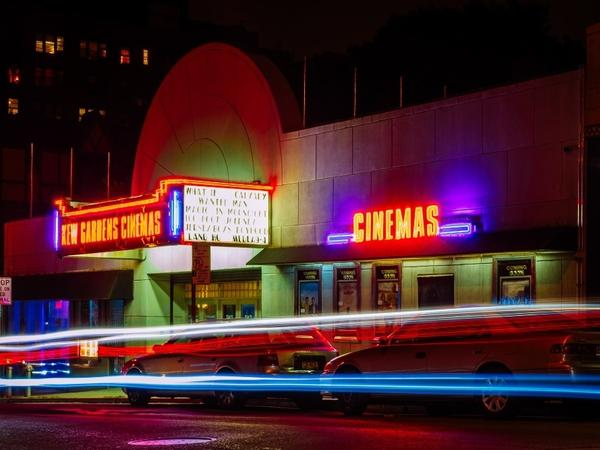A cinema with colorful neon lights, presenting the best films.