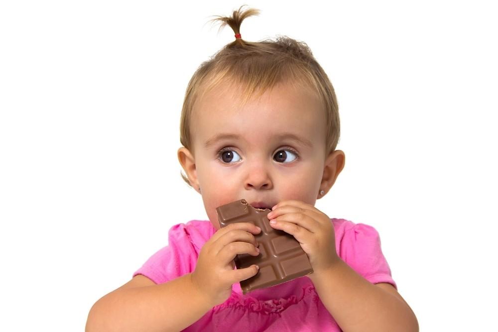 Sweet baby girl eating chocolate.