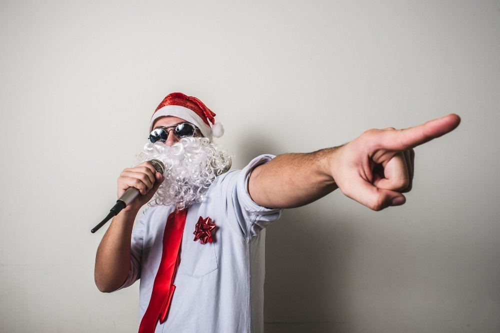 A funny man with a Santa's beard pointing with his hand.