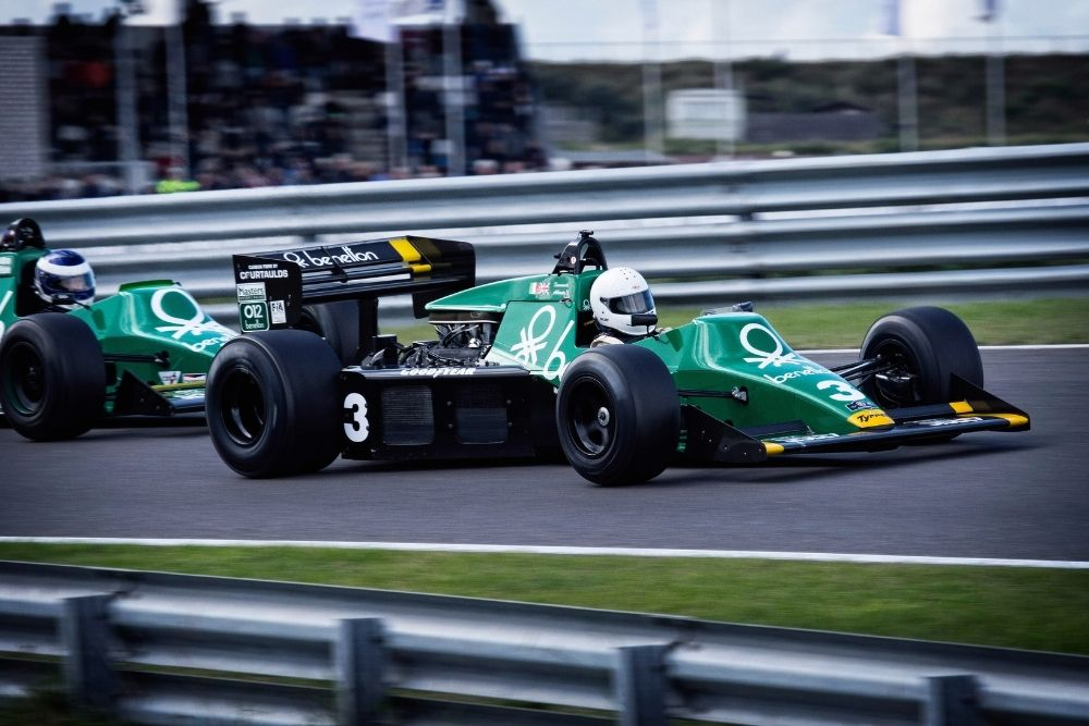 An f1 green car in a middle of a race.