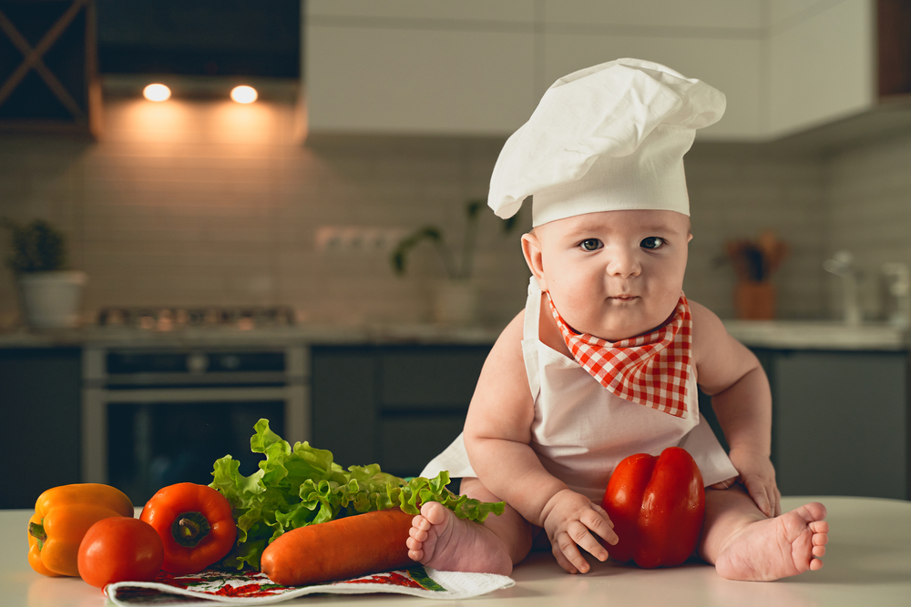 Cute baby dressed as a chef with food around him.