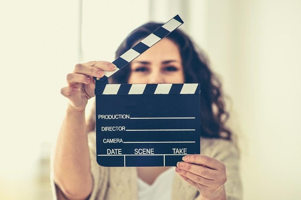 An actress hiding behind a movie clapper.