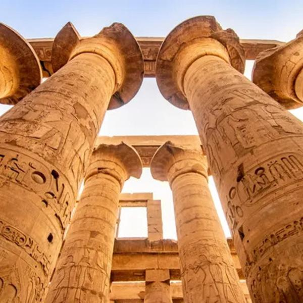 Ancient historical columns inside beautiful Egyptian landmarks with hieroglyphics.