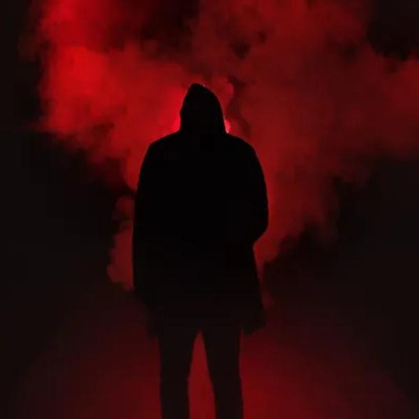 A scary scene from Typical of Horror movies of a shadow man stands in a smoke.