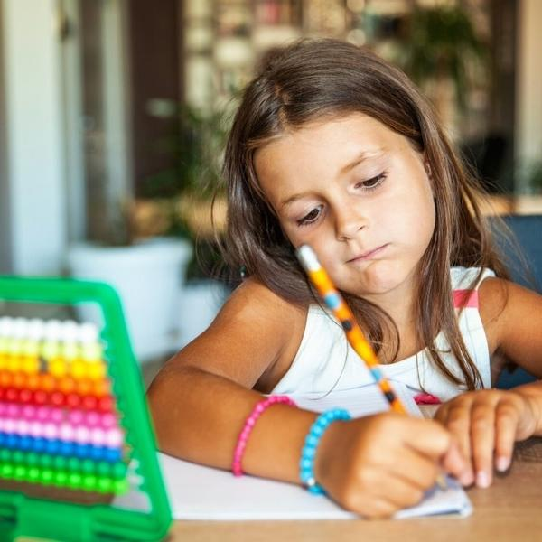 A little girl writing answers to a math question.