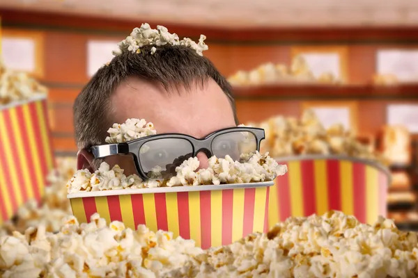 Man in glasses in a bucket of popcorn watching a movie.