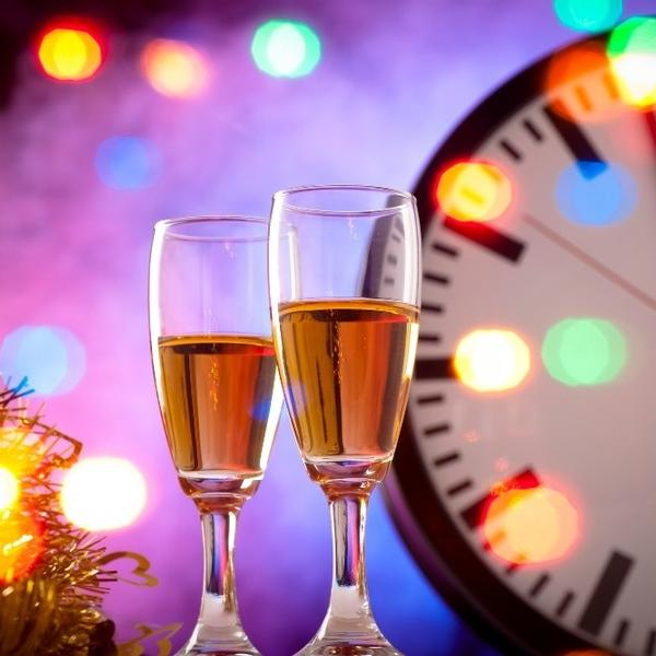 New years eve with two glass of champagne and a clock counting down.
