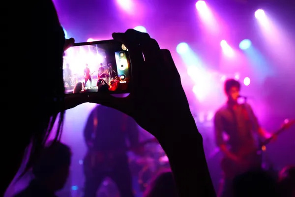 Typical Pop Culture moment of a fan picturing is a favorite music band with the smartphone.