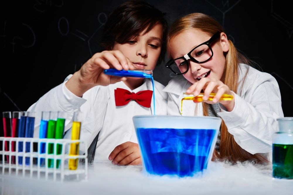 Two kids doing a small science experiment with blue liquid.