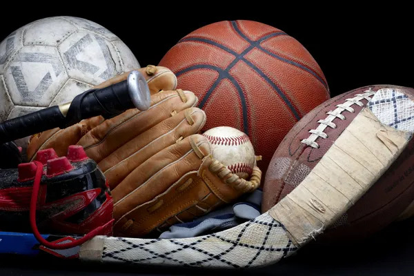 Close up shot of old soccer ball, basketball, baseball, football, bat, hockey stick, baseball glove and cleats.