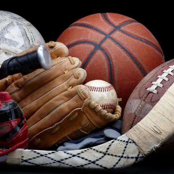 Close up shot of old soccer ball, basketball, baseball, football, bat, hockey stick, baseball glove and cleats.