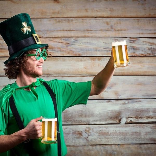 A young man dressed in green for St. Patrick raising his beer glass and saying cheers.
