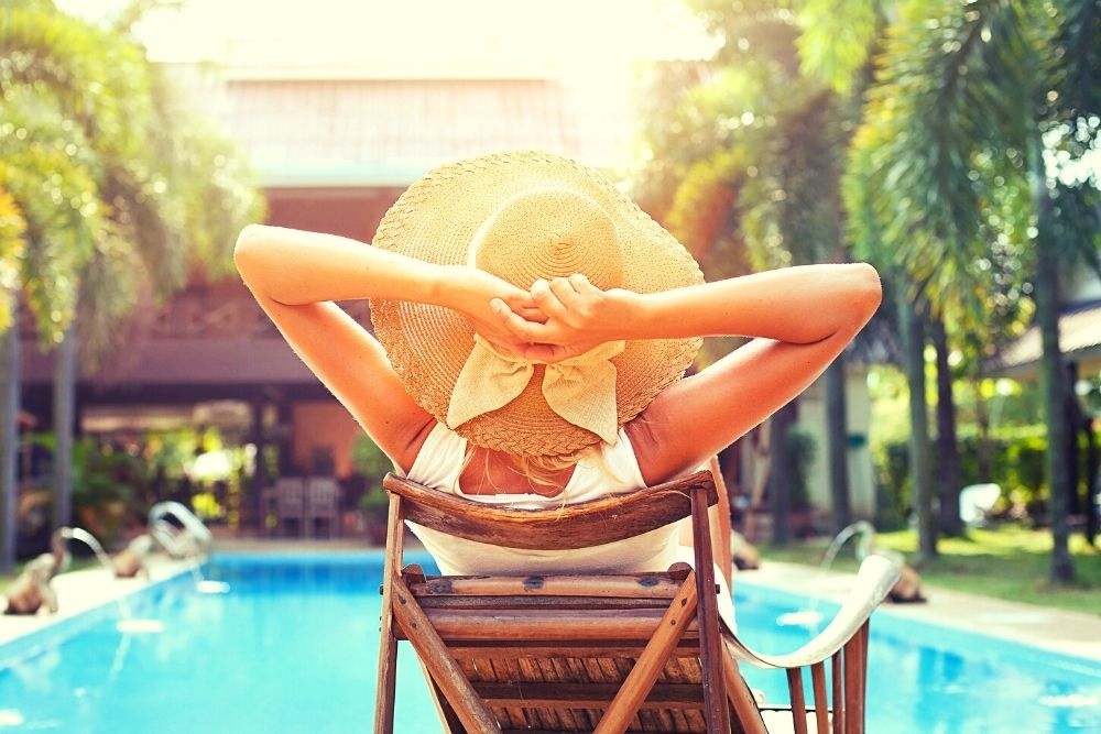 A woman is sitting in the pool and getting tanned in the summer.