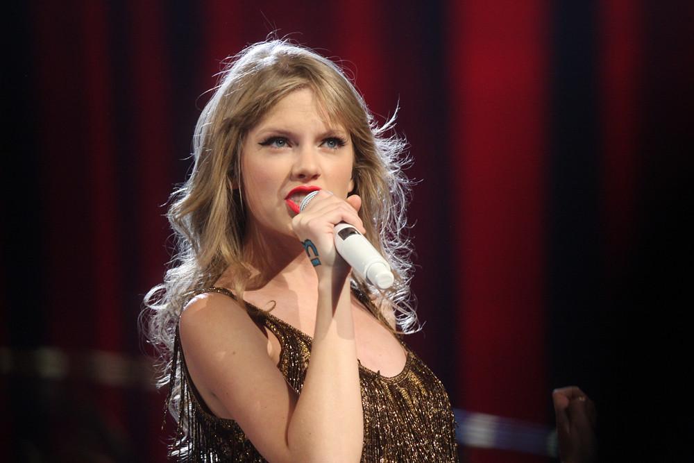 Taylor Swift singing in a golden dress, in Sydney, Australia