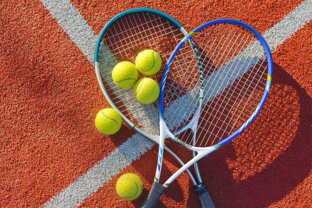 A tennis ball, tennis bat on a tennis clay court.