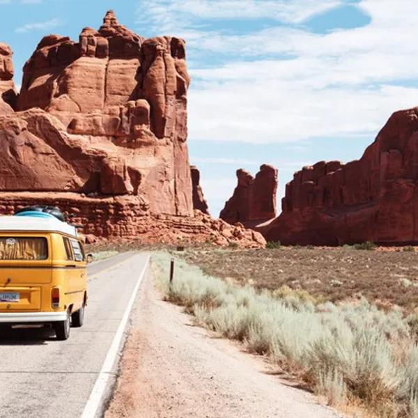 A big yellow old van traveling in a united states national park