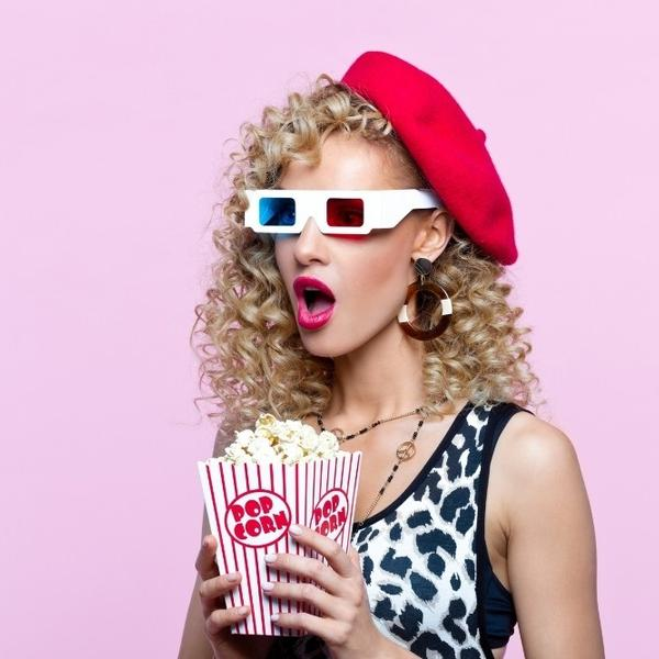A woman dressed up in 1980s style watching movies and eating popcorn.