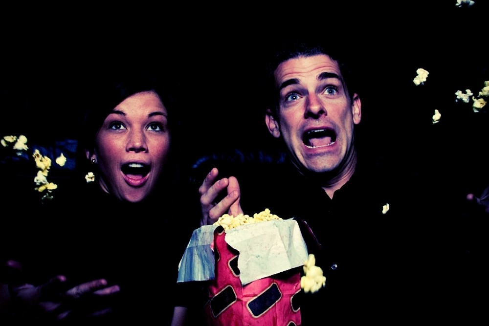 A couple watching a 90s movie and eating popcorn.