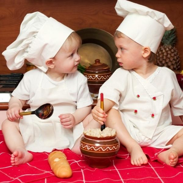 Two cute babies dressed up a chefs, cooking in the kitchen.
