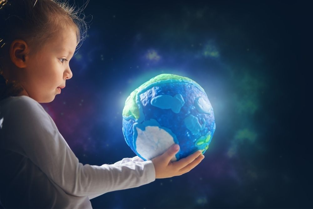 A little boy is holding a childish Earth in his hands.