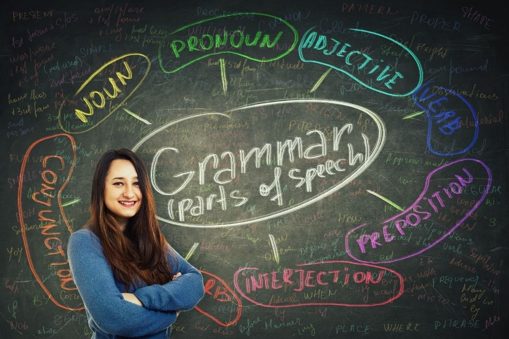 A girl is standing near a green chalkboard with English grammar examples