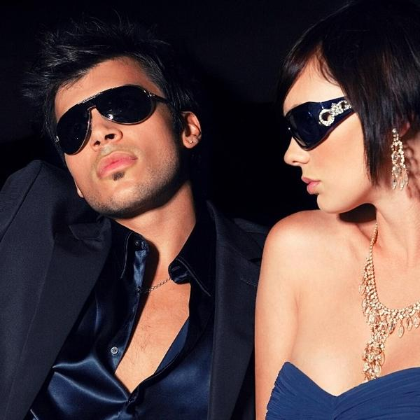 A Famous Couple of two celebrities, in a car,  with dark sunglasses.