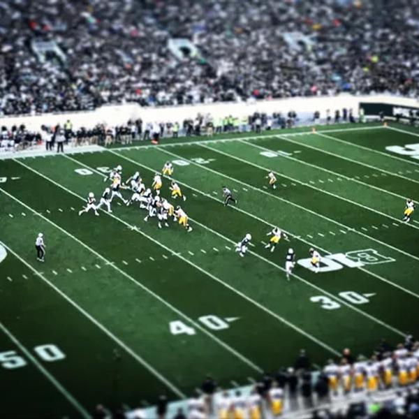 A Football court in an NFL game with many fans.