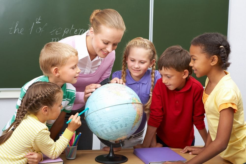 Kids and their geography teacher learning geography on the globes ball.