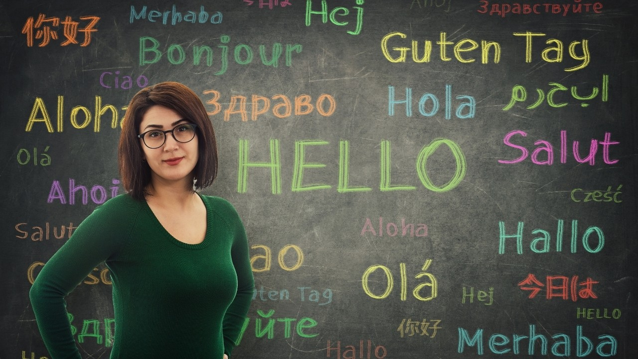 A language teacher with the word hello in many languages on the chalkboard.