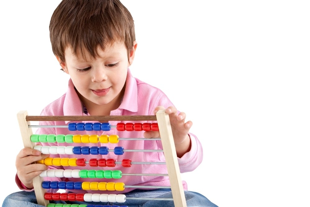 A cute 3th-grade boy playing with math toys for kids.