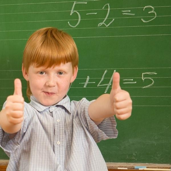 A redhead 4th-grade boy is thinking and looking on a green math chalkboard with thumbs up.