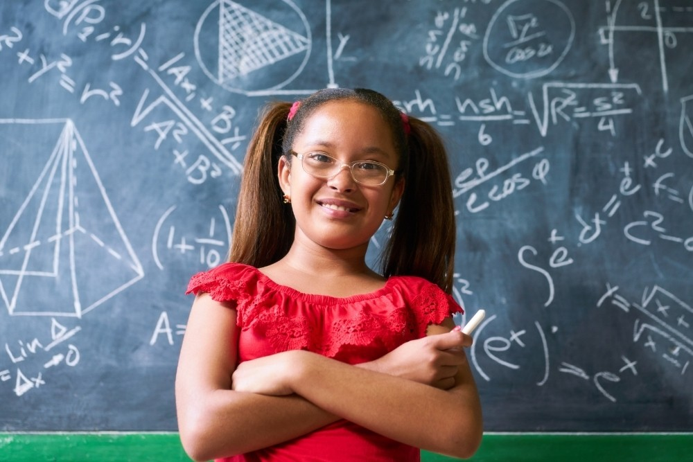 A cute 6th-grade girl in a red dress, with a math chalkboard behind her