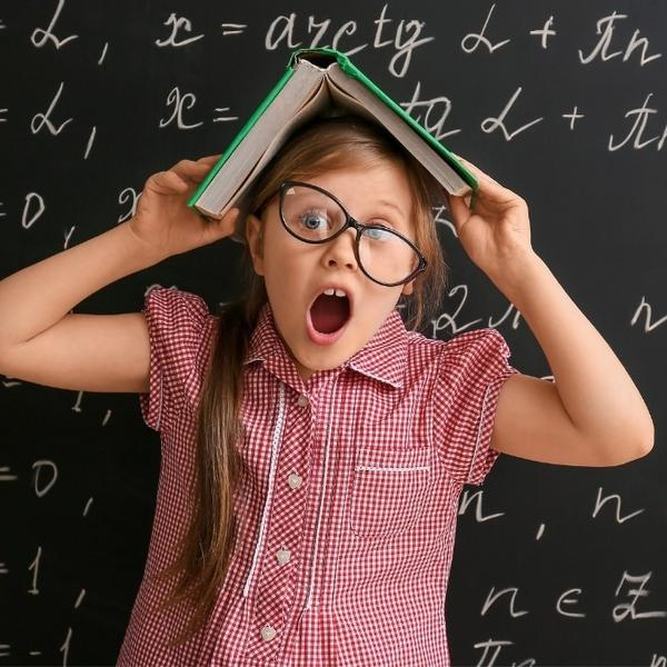 A funny girl with a multiplication math book on her head.