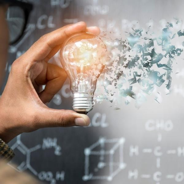 An hand holding a light bulb in a physics experiments.