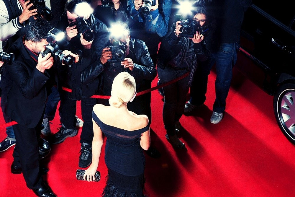 Photographers take images of a celebrity on the red carpet.