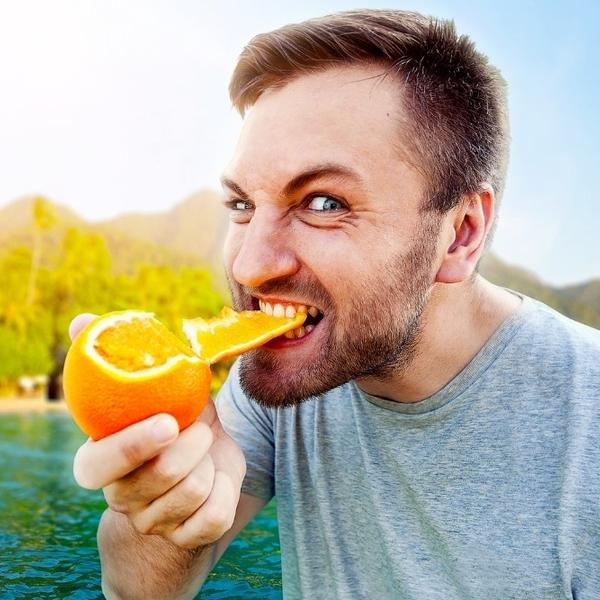 A man eating an orange and more food.