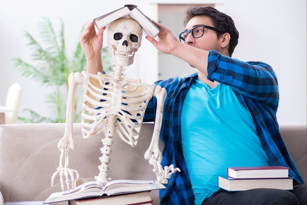 A funny person play with the skeleton will learning on the human body.
