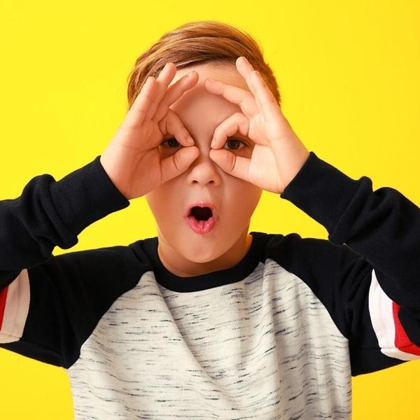 A cute kid doing the shape of glasses with his hands on his face.