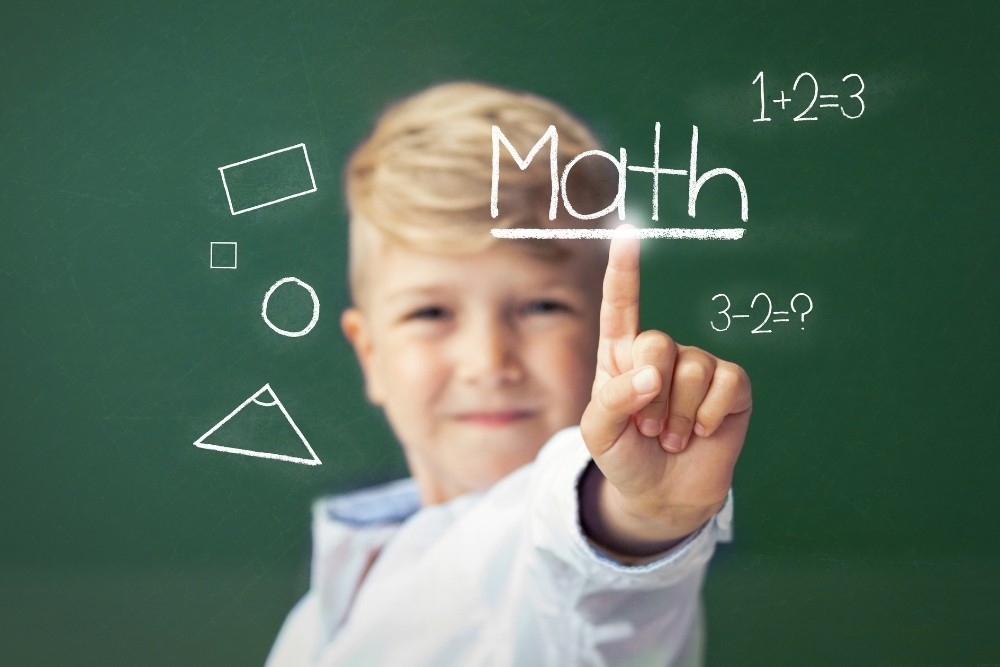 A kid with a math chalkboard pointing on the word Math.